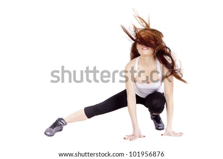 Woman exercises. Young woman stretching muscles and tendons during exercise. It is happy and smiling. She has dispelled hair.