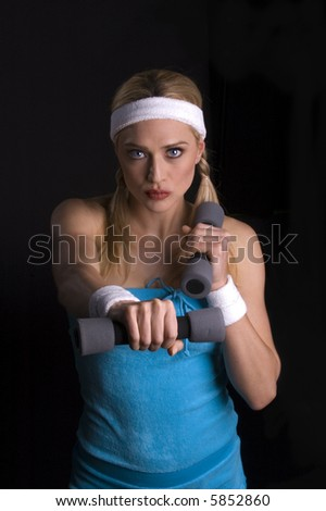 Woman exercising against a black background - stock photo