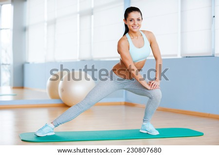 Woman exercising. Beautiful young woman in sports clothing doing stretching exercise and smiling while standing in health club