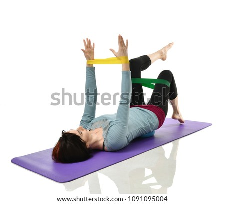 Woman exercising doing postnatal workout. Female fitness instructor working out with a rubber resistance band isolated on white background   #1091095004