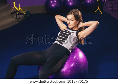 Woman exercising her abs on a Pilates ball. Natural light. Shallow DOF. #1015770175