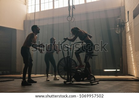 Woman exercising on air bike at gym with friends motivating. Female using air bike for workout at cross training gym with friends. #1069957502