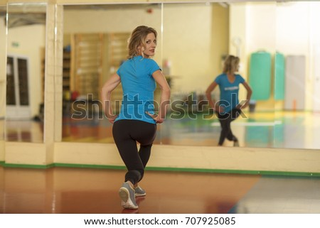 woman exercising on mat in fitness class. Female workout pilates squats lungs back shot #707925085