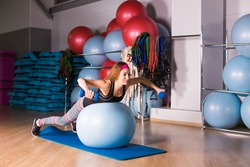Woman exercising with dumbbells on a fitness ball