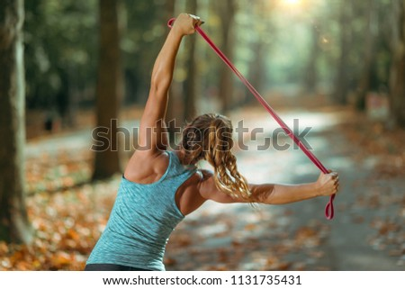 Woman Exercising With Elastic Band Outdoors in The Fall, in Public Park