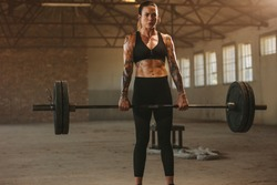 Woman exercising with heavy weights in old warehouse. Tattooed female doing deadlift workout with barbell in an abandoned warehouse.