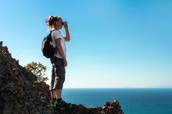 Woman explorer hiker with backpack on edge of cliff in mountains looking away through binoculars at blue sea. Independence and freedom.