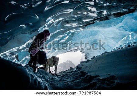 Woman exploring athabasca glacier cave in banff / jasper national park canada with  adventurous dog pet