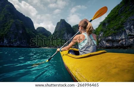 Woman exploring calm tropical bay with limestone mountains by kayak. Ha Long Bay, Vietnam #266996465