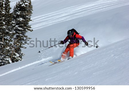 Woman extreme skiing down a slope in the Utah Mountains, USA.
