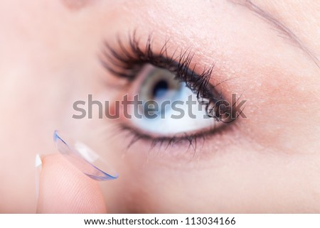 Woman eye with contact lens applying, macro