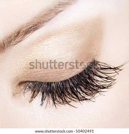 Woman eye with extremely long eyelashes. Delicate pastel shades. Focus mostly on eyelashes