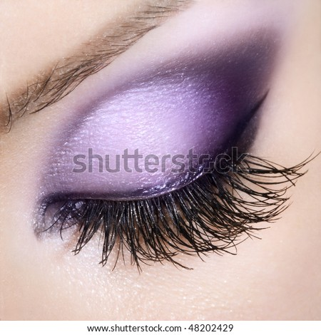 Woman eye with extremely long eyelashes. Purple makeup.