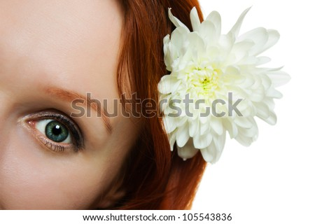 Woman eye with natural looking makeup and white chrysanthemum