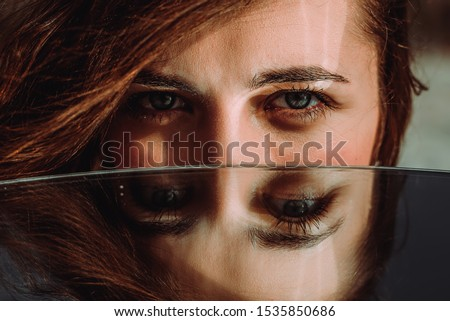 Woman eyes close up reflected in mirror. Hypnotize strong look. Hypnotic deeply penetrating glance. Revengeful insidious expectant gaze. Young caucasian girl face. Horizontal portrait. Good vision Stock photo ©