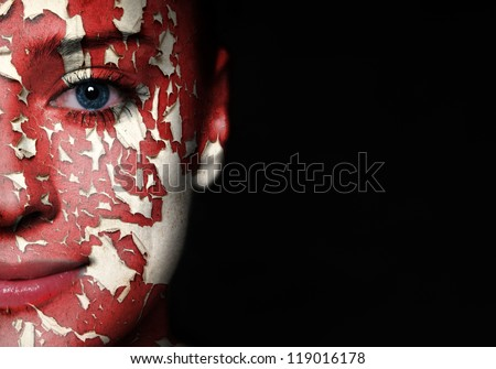 Woman face covered with old cracked red paint
