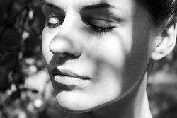 Woman face in monochrom close up in the sun in the garden