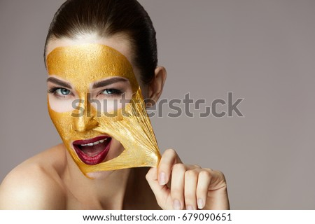 Woman Face Mask. Closeup Beautiful Sexy Girl Taking Off Cosmetic Peeling Gold Mask From Healthy Skin.   #679090651