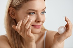 Woman Face Skin Cosmetics. Portrait Of Beautiful Sexy Girl With Hand Applying Cream Under Eyes. Closeup Healthy Young Female Holding Bottle Of Gel Near Beauty Face. Facial Cosmetics. High Resolution