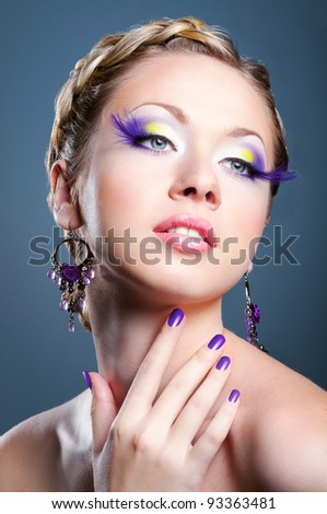 Woman face with bright violet makeup and manicure - stock photo