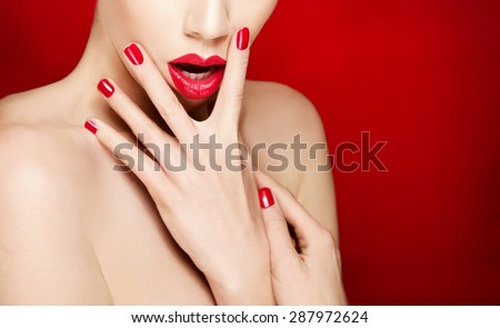 Woman face with red lips and red manicured nails. isolated on red background