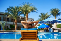 Woman faceless in hat lying on a lounger near the swimming pool at the hotel, concept summer time to travel