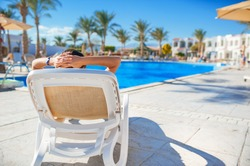 woman faceless lying on a lounger by the pool at the hotel.