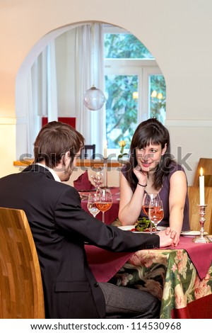 Woman facing camera and flirting with her dinner date at a romantic dinner by touching and caressing his hand across the table.