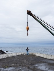 Woman far away overlooking the sea centered in the hook of a crane at the Port of Boqueirão. A place of industrial heritage. Santa Cruz das Flores, Flores Island.