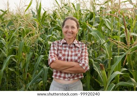 woman farmer in a field of corn cobs