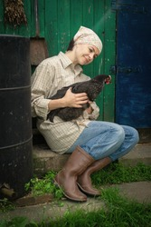 woman farmer in men's clothing, holding a black chicken in her hands in the rural scene.