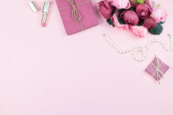 Woman fashion accessories, flowers, cosmetics and jewelry on pink background, copyspace. Womens Day concept, flat lay