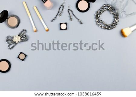 Woman fashion accessories, jewelry and cosmetics on stylish gray background. Flat lay
