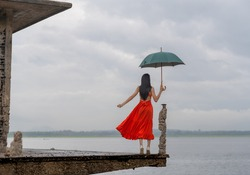 woman fashion dress standing on the retro old cottage house terrace in the lake, holding umbrella under raining season