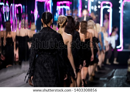 Woman Fashion Models walk back Finale on Runway Ramp during Fashion Week to present New Clothing Collection Spring Summer, on Creative Stage Catwalk with Full Scale Lighting, copy space Image