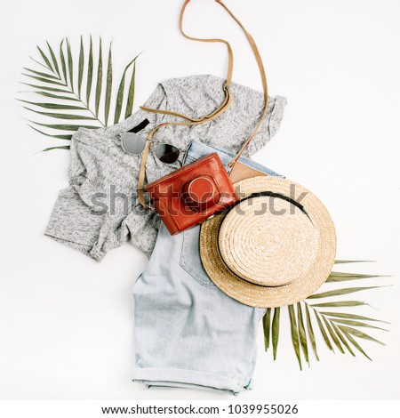 Woman fashion travel flatlay. Retro camera, straw, shorts, sunglasses and tropical palm leaf. Top view, flat lay. #1039955026