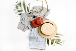 Woman fashion travel. Retro camera, straw, shorts, sunglasses and tropical palm leaf. Top view, flat lay.
