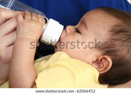 Woman feeding beautiful hispnaic infant a bottle of formula.