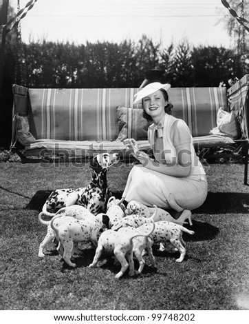 Woman feeding her dog and puppies
