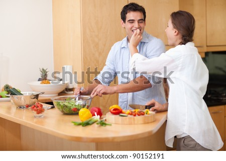 Woman feeding her husband while cooking