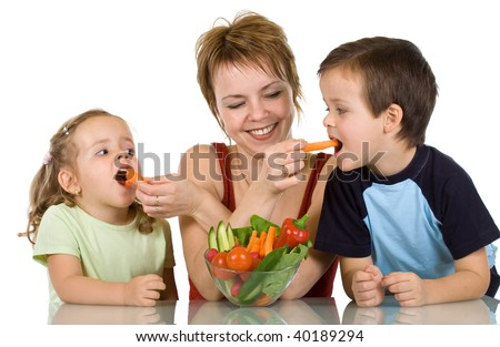 Woman feeding kids with fresh vegetables - the joy of eating healthy food - stock photo