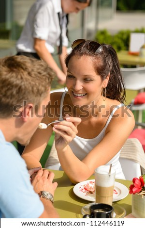 Woman feeding man cheesecake at cafe couple flirting romantic happy