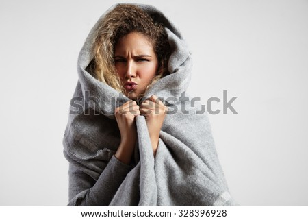 woman feeling freeze and wrap up in a blanket #328396928