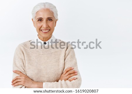 Woman feeling reliance and confidence in future. Self-assured happy and pleased senior woman with grey combed haircut, cross arms over chest like professional, standing determined white background