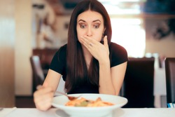 Woman Feeling Sick While Eating Bad Food in a Restaurant. Dinner customer having a bad experience feeling sick