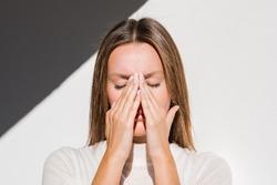 Woman feeling unwell, painful headache because of sinus ache, sinusitis, sinus pressure. Sad woman holding her nose and head because sinus pain. Coronavirus symptoms