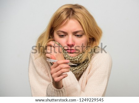 Woman feels badly ill sneezing. Girl in scarf hold thermometer and tissue close up. Measure temperature. High temperature concept. Break fever remedies. Take temperature and assess symptoms.
