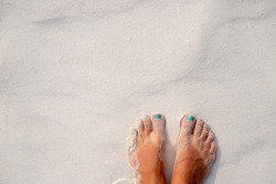 Woman feet and white sand texture. Relaxed tourist on beach. Tropical vacation banner template with text place. Summer vacation background. Bare feet girl on coral beach. Smooth sunny sand beach