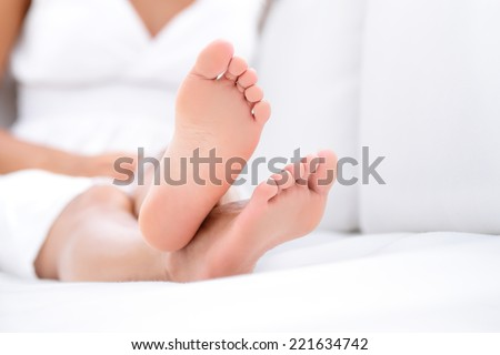 Woman feet closeup - barefoot woman relaxing in sofa. Close up of female feet of young beautiful woman sitting in couch outside.