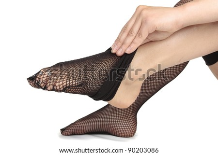 Woman feet dressing fishnet tights  over white background